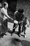 WASHING BLOOD FROM HIS HAND AFTER SLAUGHTERING A PIG FOR THE ROMANIAN ORTHODOX EASTER CELEBRATIONS. SINTESTI, ROMANIA, EASTER 1995..©JEREMY SUTTON-HIBBERT 2000..TEL./FAX. +44-141-649-2912..TEL. +44-7831-138817.
