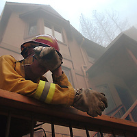 San Bernardino City Fire Capt. Steve Topoleski wipes his eyes while deceding on defending this home on Brentwood Dr. during The Grass Fire in Lake Arrowhead, Monday, Oct. 22, 2007. Eric Reed/photographer