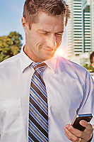 Portrait of mature attractive businessman smiling while using smartphone after work