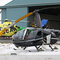 Helicopter Crash at Perth Airport, Scone….13.03.18<br />Scotland's Charity Air Ambulance pictured behind the wreckage of the Robinson helicopter which crashed shortly after 10.30am this morning at Perth Airport in Scone. The pilot was the only occupant and suffered non-life threatening injuries.<br />Picture by Graeme Hart. <br />Copyright Perthshire Picture Agency<br />Tel: 01738 623350  Mobile: 07990 594431
