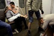Youngsters kiss and fall asleep in the Moscow metro. .The Moscow Metro, which spans almost the entire Russian capital, is the world's second most heavily used metro system after the Tokyo's twin subway. Opened in 1935, it is well known for the ornate design of many of its stations, which contain outstanding examples of socialist realist art.