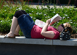 © Licensed to London News Pictures. 25/07/2012. London, UK .  A woman relaxes and reads a book in the sunshine as temperatures reach 30 degrees at Greenwhich Pier in London today 25 July 2012. Photo credit : Stephen Simpson/LNP