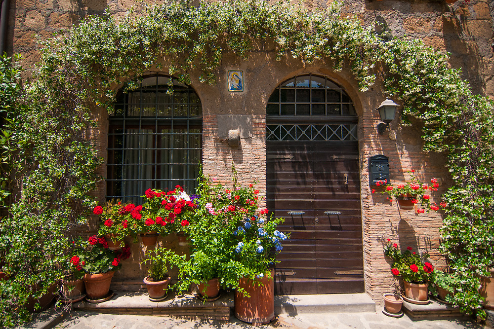 Doors and flowers of a house of the village of Civita di Bagnoregio.<br /> Civita di Bagnoregio is a town in the Province of Viterbo in central Italy, a suburb of the comune of Bagnoregio, 1 kilometre (0.6 mi) east from it. It is about 120 kilometres (75 mi) north of Rome. Civita was founded by Etruscans more than 2,500 years ago. Bagnoregio continues as a small but prosperous town, while Civita became known in Italian as La citt&agrave; che muore (&quot;The Dying Town&quot;). Civita has only recently been experiencing a tourist revival. The population today varies from about 7 people in winter to more than 100 in summer.The town was placed on the World Monuments Fund's 2006 Watch List of the 100 Most Endangered Sites, because of threats it faces from erosion and unregulated tourism.