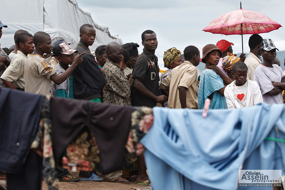 Displaced people wait in line to receive coupons during a non-food item fair at the Miketo IDP settlement, Katanga province, Democratic Republic of Congo on Sunday February 19, 2012. Displaced people who have lost most of their belongings as they fleed their homes receive coupons their can exchange for goods at a fair held in partnership with local traders.