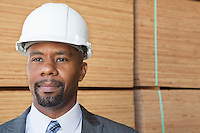 Confident African American male contractor looking away with stacked wooden planks in background