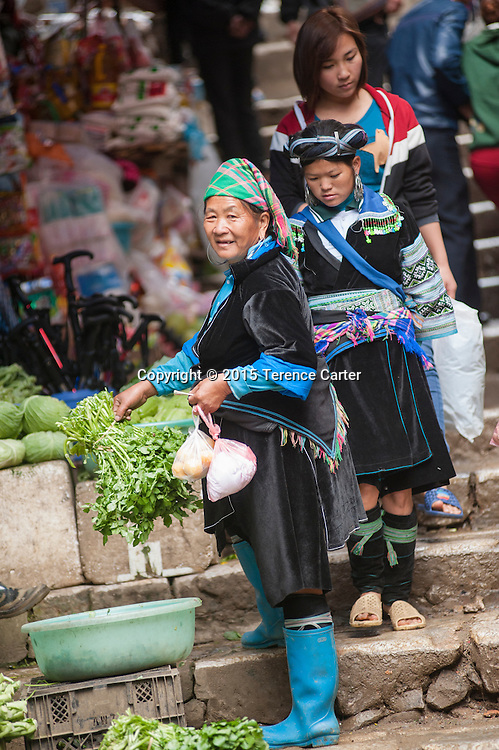 A hilltribe woman buys herbs in the markets of Sapa, Vietnam.