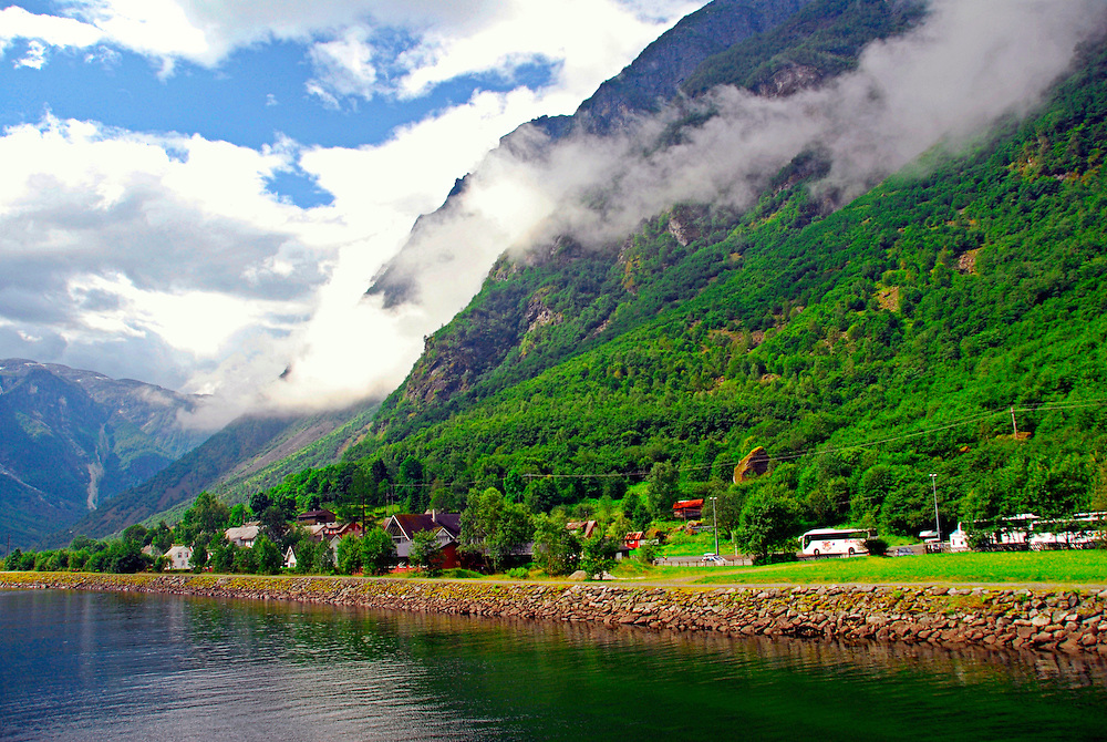 "The village of Bakka, located on the west shore of the Sognefjord. The Sognefjord is the largest fjord in Norway, and the second longest in the world. Located in Sogn og Fjordane county, it stretches 205 kilometers (127 mi) inland to the small village of Skjolden. The fjord takes its name from the traditional district of Sogn. The Naeroyfjord is a fjord in the municipality of Aurland in Sogn og Fjordane, Norway. The narrow fjord is a branch of the large Sognefjord, and it is featured on the ""Norway in a Nutshell"" daytrips for tourists. The 18-kilometre (11 mi) long fjord is only 500 meters (1,600 ft) wide in some parts. The river Naeroydalselvi flows down the valley Naeroydalen into the fjord at the village of Gudvangen, near the highway E16. Since 2005, the Naeroyfjord has been listed as a UNESCO World Heritage Site. It has also been rated by the National Geographic Society as the world's number one natural heritage site along with the Geirangerfjord. The voyage with the car ferry ends at the village Flam. Flam is a village at the inner end of the Aurlandsfjord, an arm of the Sognefjord. The village is located in the municipality of Aurland in Sogn og Fjordane county, Norway. The village is located along the E16 highway, about 7 kilometers (4.3 mi) southwest of Aurlandsvangen, 12 kilometers (7.5 mi) south of Undredal, and 15 kilometres (9.3 mi) east of Gudvangen(through the Gudvanga Tunnel)."