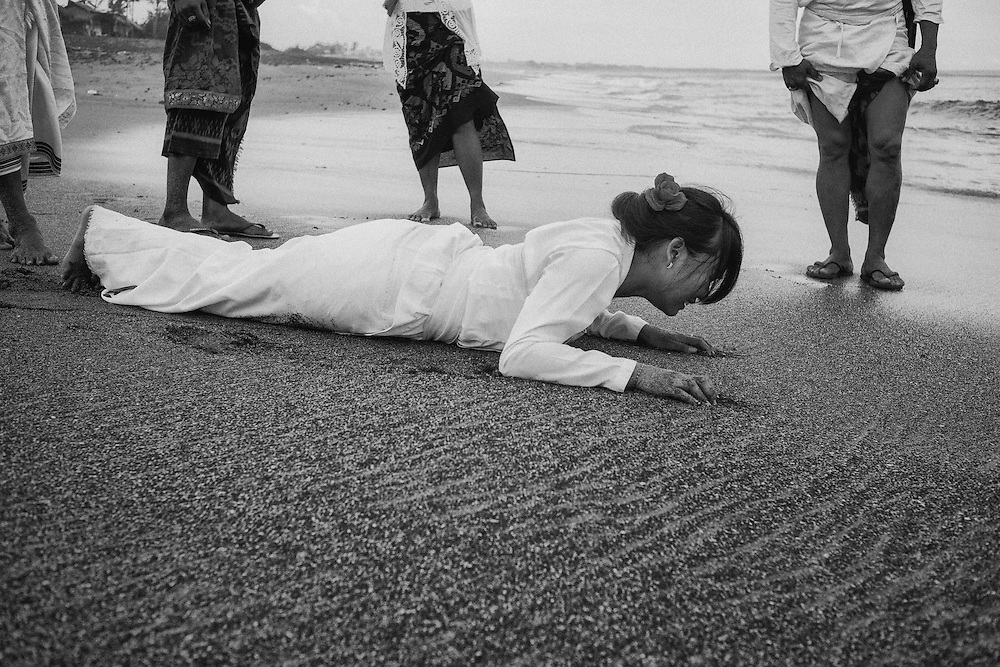 A woman in a state of trance crawled to the water.  <br /> <br /> Melasti is a Hindu Balinese purification ceremony and ritual, which according to Balinese calendar is held several days prior to the Nyepi holy day.  Melasti was meant as the ritual to cleanse the world from all the filth of sin and bad karma