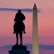 The Ulysses S. Grant memorial near the US Capitol is framed along with the Washington Monument against a pink evening sky in Washington, DC.