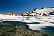Woman swims in icy Lake Aloha in the Desolation wilderness area in south lake tahoe.