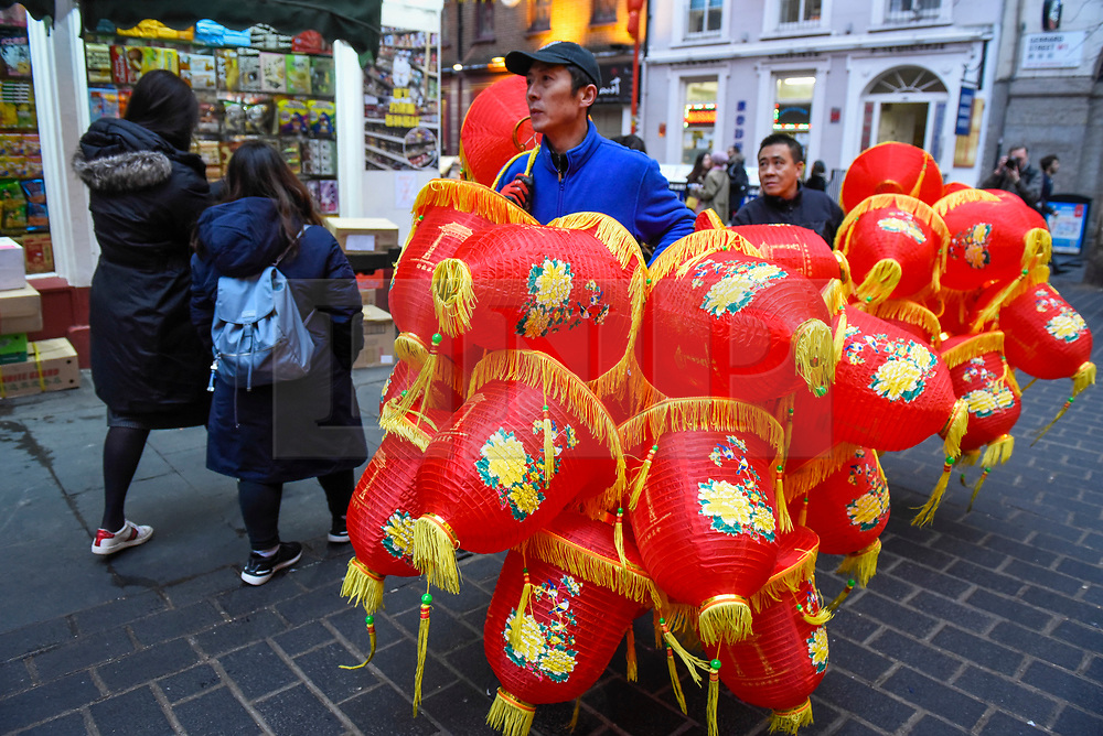 © Licensed to London News Pictures. 24/01/2020. LONDON, UK.  A workman prepares to hang red lanterns in Chinatown ahead of Chinese New Year, the Year of the Rat. Photo credit: Stephen Chung/LNP