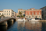 A deep red Venetian style building in the harbour in Ortigia, Syracuse, Sicily, Italy