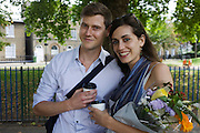 A romantic couple walk through London Fields in the London borough of Hackney where, a week before, looters were robbing residents during the London riots.