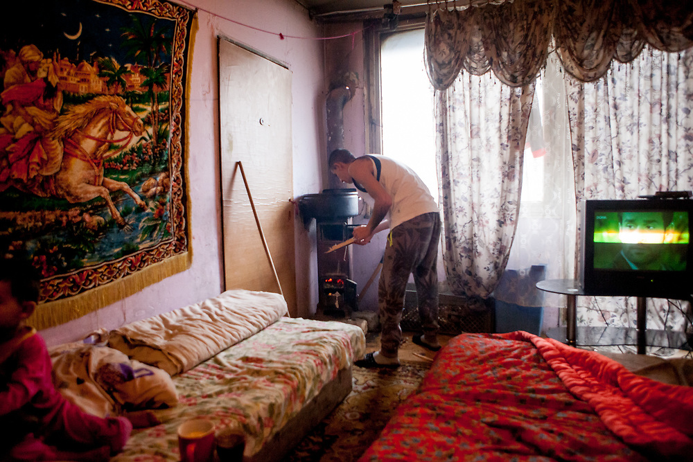 Ondrej (30) is doing fire in the living room of his family in a building at Lunik IX. He is living with his wife Adriana (25), his two children, his parents and grandmother in this flat.
