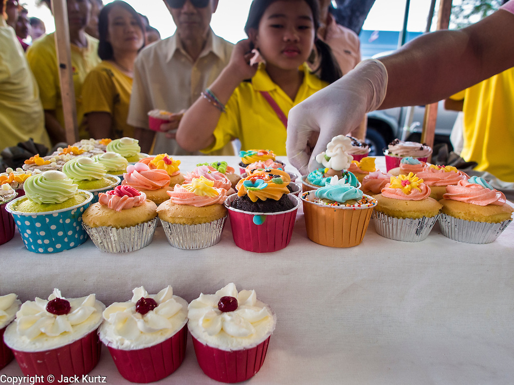 05 DECEMBER 2013 - BANGKOK, THAILAND: Thai get free cupcakes at the celebration of the King's Birthday. Thais observed the 86th birthday of Bhumibol Adulyadej, the King of Thailand, their revered King on Thursday. They held candlelight services throughout the country. The political protests that have gripped Bangkok were on hold for the day, although protestors did hold their own observances of the holiday. Thousands of people attended the government celebration of the day on Sanam Luang, the large public space next to the Grand Palace in Bangkok.     PHOTO BY JACK KURTZ