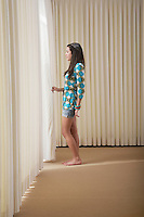 Teenage girl (16-18) standing in empty room drawing aside blinds side view