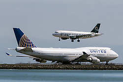 Frontier Airlines Airbus A319-111 (N935FR) lands past United Airlines Boeing 747-422 (N174UA) at San Francisco International Airport (SFO), Millbrae, California, United States of America