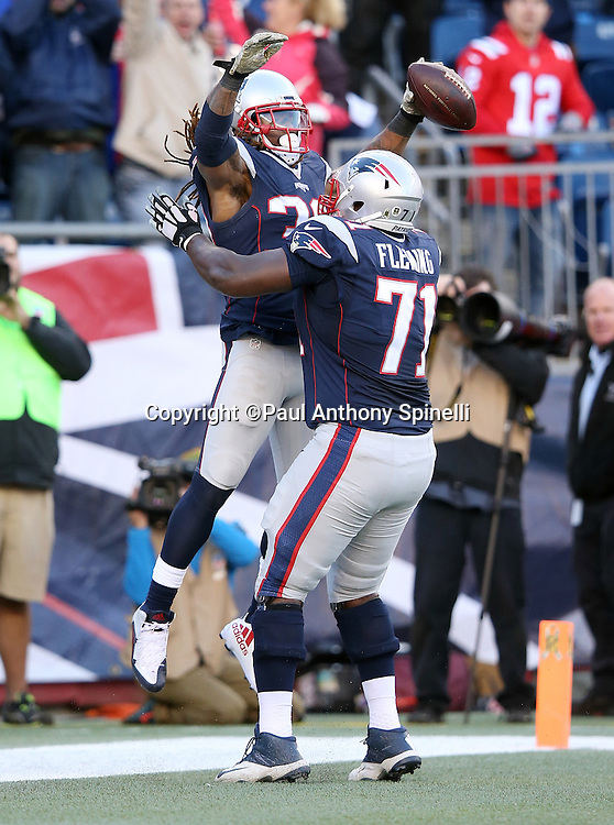 New England Patriots running back Brandon Bolden (38) celebrates as he leaps into the arms of New England Patriots offensive tackle Cameron Fleming (71) after catching an 18 yard touchdown pass that gives the Patriots a 27-3 lead during the 2015 week 9 regular season NFL football game against the Washington Redskins on Sunday, Nov. 8, 2015 in Foxborough, Mass. The Patriots won the game 27-10. (©Paul Anthony Spinelli)