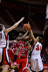 04 December 2009: Guarded by Nicolle Lewis and Hannah Spanich, Ebony Lewis struggles up with a shot knocking team mate Marke Freeman away.The Huskies of Northern Illinois University fall to the Redbirds of Illinois State University by a score of 85-57 on Doug Collins Court in Redbird Arena in Normal Illinois.