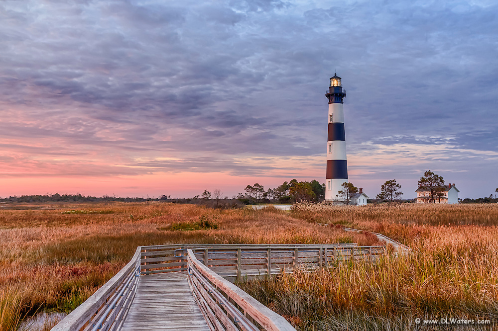 A walkway through the marsh leading to Bodie Island Lighthouse at sunrise.