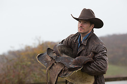 cowboy holding a saddle in the rain
