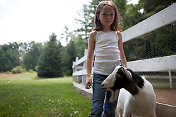 Young Girl and Goat Standing By Fence