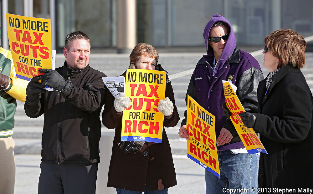 Rick Moyle (from left), Executive Director of Hawkeye Labor Council, Shelley Parbs, President of Hawkeye Labor Council, and Devin Mehaffey, member of SEIU local 199, listen to Colleen Mehaffey, member of SEIU local 199, talk about the effects of the sequestration as they hold up signs at a rally organized by the Hawkeye Labor Council and the AFL-CIO to call on Congress to repeal the sequestration in front of the US District Court in Cedar Rapids on Wednesday, March 20, 2013.