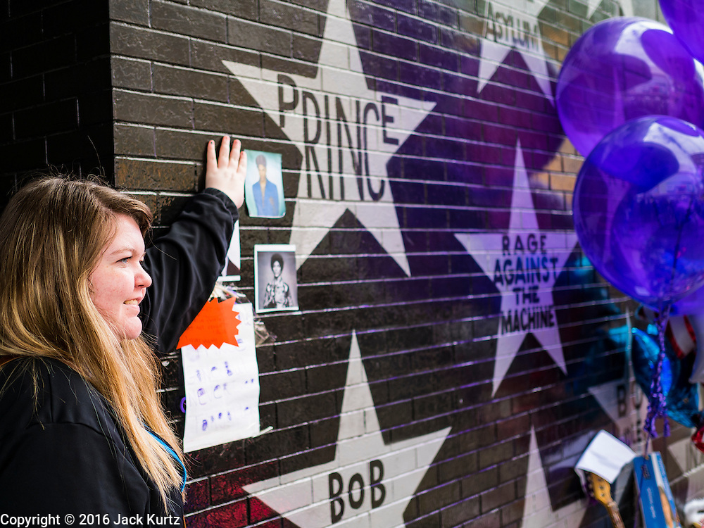 """22 APRIL 2016 - MINNEAPOLIS, MN: A woman touches the star for Prince at a memorial to Prince in front of 1st Ave in Minneapolis. Thousands of people came to 1st Ave in Minneapolis Friday to mourn the death of Prince, whose full name is Prince Rogers Nelson. 1st Ave is the nightclub the musical icon made famous in his semi autobiographical movie """"Purple Rain."""" Prince, 57 years old, died Thursday, April 21, 2016, at Paisley Park, his home, office and recording complex in Chanhassen, MN.    PHOTO BY JACK KURTZ"""