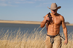 very sexy cowboy without a shirt walking through tall grass by a lake in New Mexico