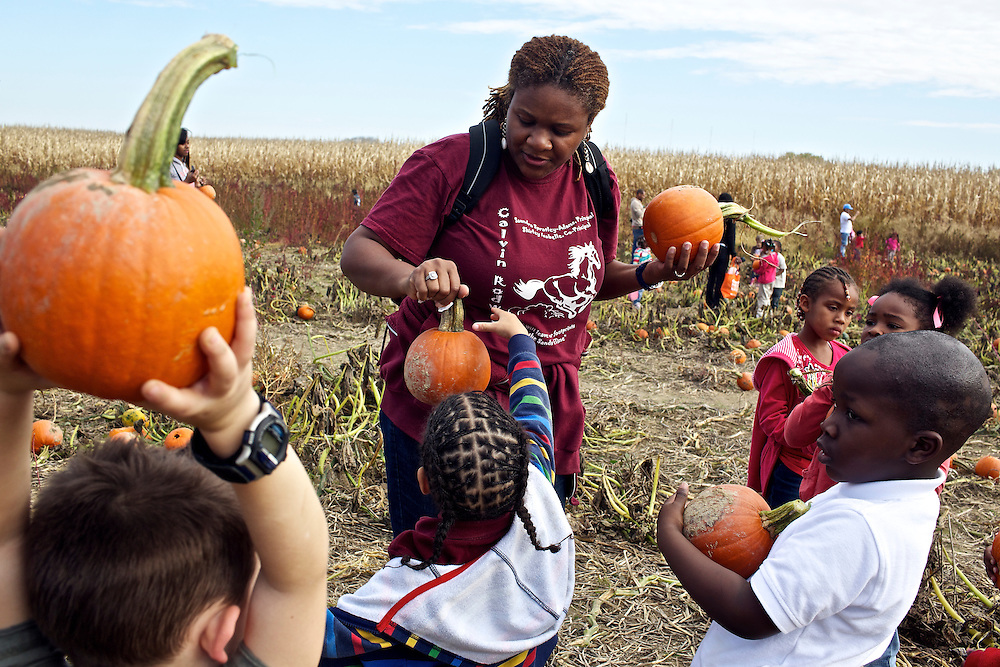 """Calvin Rodwell Elementary School Pre-kindergarten teacher Erika Parker, left, helps students select a pumpkin to take home at Summers Farm in Frederick, MD on Oct. 24, 2012. The visit to the farm was part of a """"Common Core"""" reading and learning unit for their class, which aims to follow up non-fiction reading with learning in the field. The day prior the children read a book about going to a farm."""