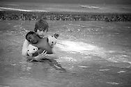 A student from Waterford Kamhlaba college swimming with an orphaned child from ward 8 of the Government Hospital at Mbabane, Swaziland during a swimming trip for children born HIV+. The Kingdom of Swaziland (population 1.1m), a small, landlocked country in southern Africa was bordered by South Africa on three sides and Mozambique to the east, with Mbabane as its administrative capital. At the start of the 21st century, the country had the highest incidence per head of population of HIV/Aids in the world and and high levels of poverty mainly in rural areas where 75 per cent of the population lived.