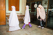 """11 JANUARY 2013 - BANGKOK, THAILAND:   Girls from a neighborhood Muslim school walk into a Mosque for noon prayers in the Ban Krua neighborhood in Bangkok. The Ban Krua neighborhood of Bangkok is the oldest Muslim community in Bangkok. Ban Krua was originally settled by Cham Muslims from Cambodia and Vietnam who fought on the side of the Thai King Rama I. They were given a royal grant of land east of what was then the Thai capitol at the end of the 18th century in return for their military service. The Cham Muslims were originally weavers and what is known as """"Thai Silk"""" was developed by the people in Ban Krua. Several families in the neighborhood still weave in their homes.       PHOTO BY JACK KURTZ"""