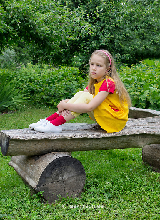 Caucasian girl sitting on old wooden bench in backyard. Serious mood. Green, grass, lawn and seating.