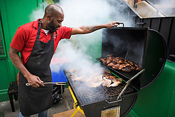 © Licensed to London News Pictures. 24/08/2018. London, UK. Jerk Chicken being prepared on a grill at a Jamaican restaurant in Notting Hill, West London ahead of the 2018 Notting Hill Carnival which starts this weekend. Photo credit: Ben Cawthra/LNP