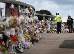© Licensed to London News Pictures. 02/09/2015. Shoreham, UK. Policemen look at floral tributes placed on a bridge near the site of the crashed Hawker Hunter fighter jet. The aircraft crashed while performing at the Shoreham air show on August 22, 2015 killing 11 people on the ground. As an inquest into the deaths opened today in nearby Horsham, the name of the last of the victims Graham Mallinson was released.  Photo credit: Peter Macdiarmid/LNP