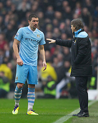 MANCHESTER, ENGLAND - Sunday, January 8, 2012: Manchester City's Aleksandar Kolarov and manager Roberto Mancini  against Manchester United during the FA Cup 3rd Round match at the City of Manchester Stadium. (Pic by Vegard Grott/Propaganda)