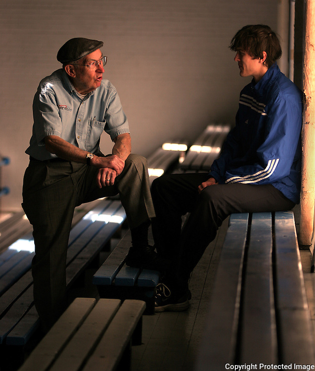 Drake sports historian Paul Morrison, left, visits with a member of the Bulldog's track team.  Morrison saw his first Drake Relays in the 1930's.  One of his memories includes watching the great Jesse Owens win the Drake Relays 100 yard dash.  photo by david peterson