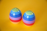 Multi-coloured salt and pepper shakers on a yellow background