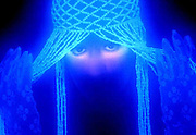 Close shot of a young woman with glowing headpiece and gloves and highlighted eyes.Black light