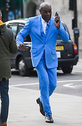 © Licensed to London News Pictures. 13/12/2018. London, UK. .Former WBC heavyweight boxing champion, FRANK BRUNO MBE is seen talking on his phone while walking through Westminster wearing a bright blue suit on December 12, 2018. Photo credit: London News Pictures Ltd