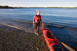 A woman prepares to kayak on the coast of New Castle, New Hampshire.