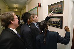 Group of secondary school students looking at an old school photo in the corridor,