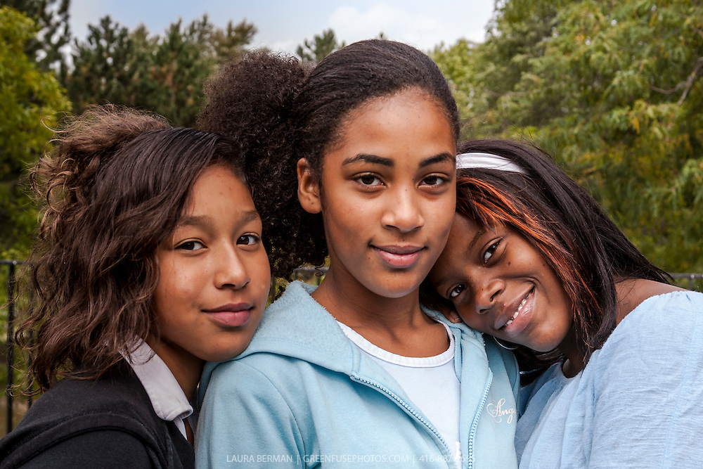 Three African-American teenage girls. One girl is in the center while her two friends lean on either side of her. Their closeness and friendship is evident in their attitudes.