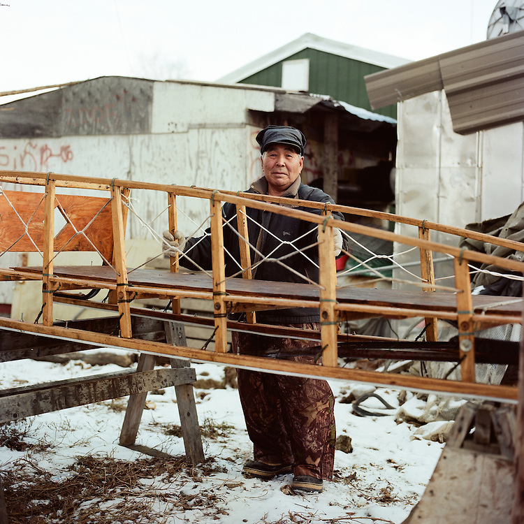 """These are my dad's old sleds. The runners are bent, so I am taking it apart to rebuild it. I have been building sleds for quite a while. My dad taught me; he would watch me and when I would make a mistake, he would straighten me out, which was good, you know. He would watch and tell me, ""you're not doing it right, right there"" and either I would take it apart or just keep on building. I would try not to get mad. Then I had to do it right, which is good. The airfare is getting pretty high here and the gas. So, it's better off to get some dogs I think, and a lot cheaper. We have seven of our own kids and we adopted five more girls. We have a big family."" —Oscar Griest Sr., is Inupiaq from Shungnak, Alaska. He is working on a handmade sled to pull behind his snow machine. Similar types of sleds are used for dog mushing."