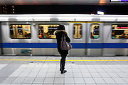 A women waits for the arriving MRT train.
