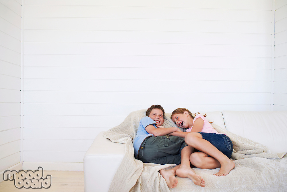 Young boy and girl laughing on couch in weatherboard room