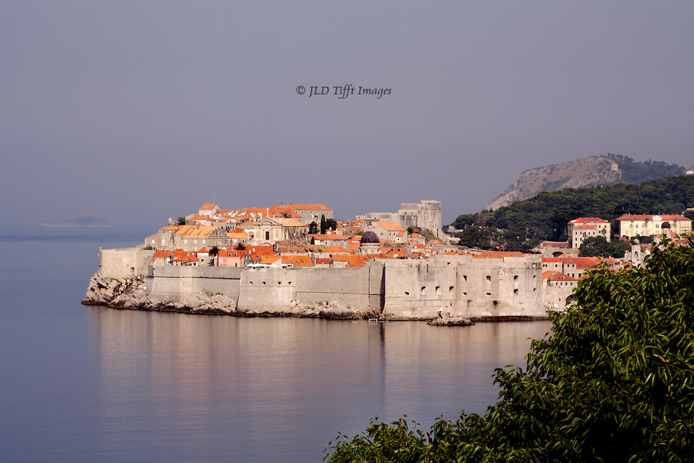 Distant view of Dubrovnik from along the coast to the south of the city.  Its walls and orange rooftops glow in the sun.