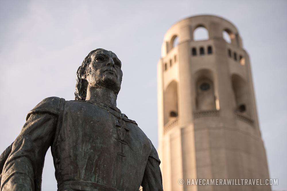 In the foreground is a bronze statue of Christopher Columbus by Vittorio Colbertaldo. in the background is the top of Coit Tower on top of Telegraph Hill in San Francisco, California. The tower was built in 1933 from funds bequeathed by Lillie Hitchcocl Coit.