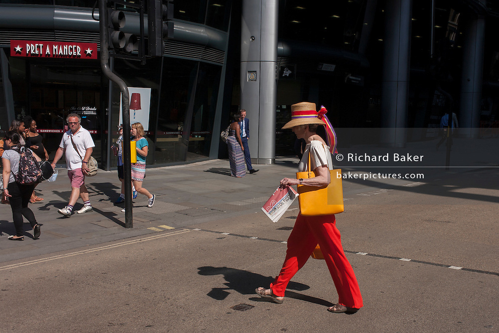 An eccentrically-dressed lady crosses Cannon Street in the City of London, UK.
