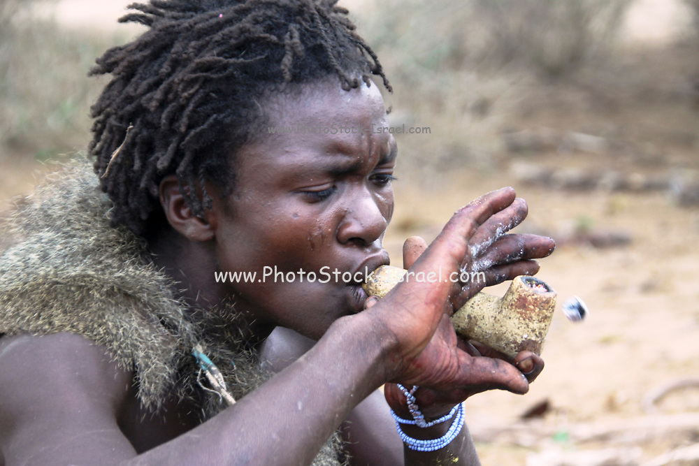 Hadza man smoking from a traditional clay pipe Photographed near Lake Eyasi, Tanzania, Africa